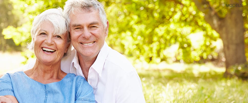 Mature Couple Smiling Outdoors With Green Tree in Background
