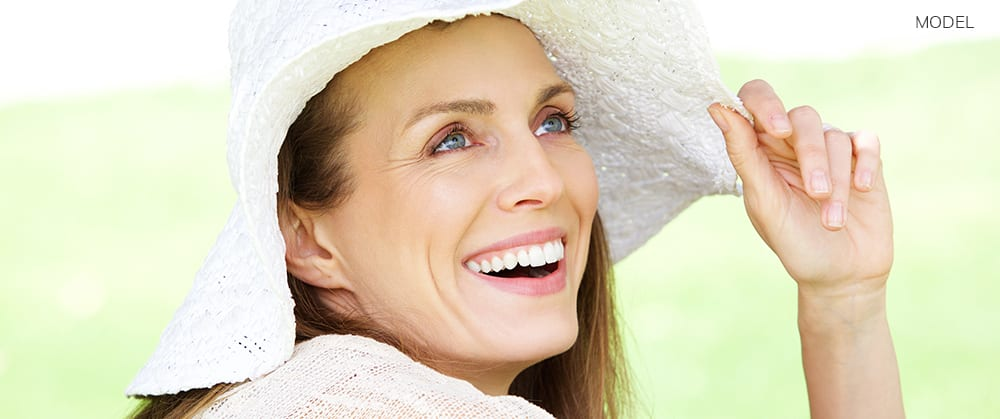 Close up portrait of a natural woman smiling with hat